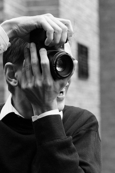 man with camera over his face