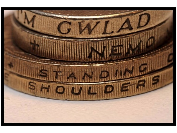 Photo of the edge of coins, with the words *Standing On* and *Shoulders* visible