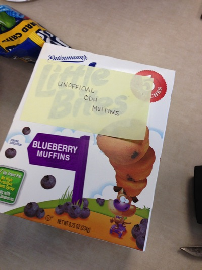 A box of muffins with a postit note that says,