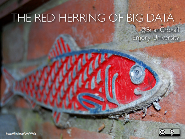 A red, metal fish on a brick wall