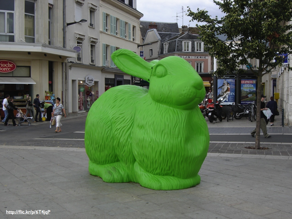 A large green plastic bunny statue in a city square