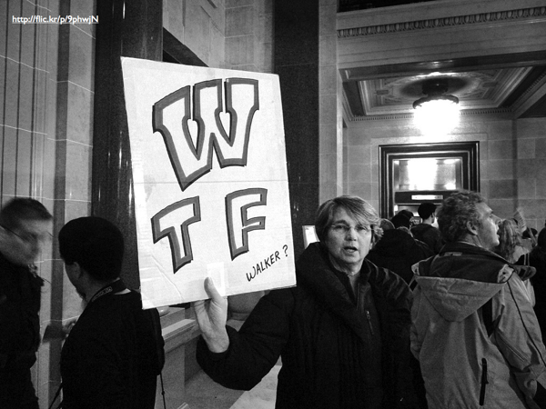 A protestor holding up a banner that reads 'WTF Walker?'