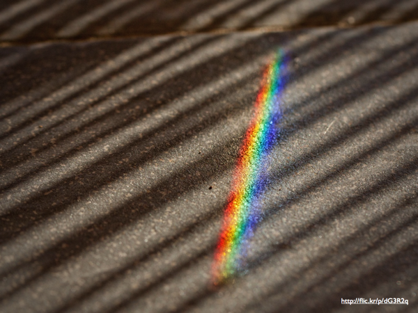A rainbow cast from a prism on a sidewalk