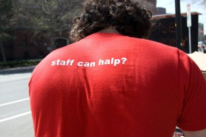 "Man wearing a shirt that reads ""staff can halp?"" on the back."