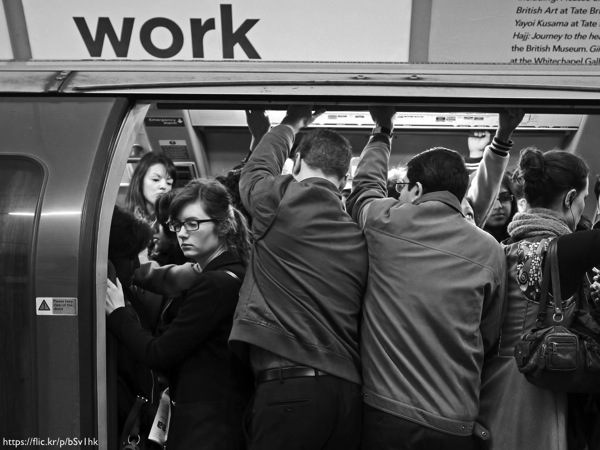 A crowded subway car with the word 'Work' written above it