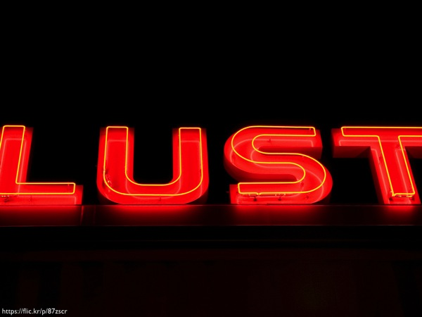 The word 'lust' written in red neon lights