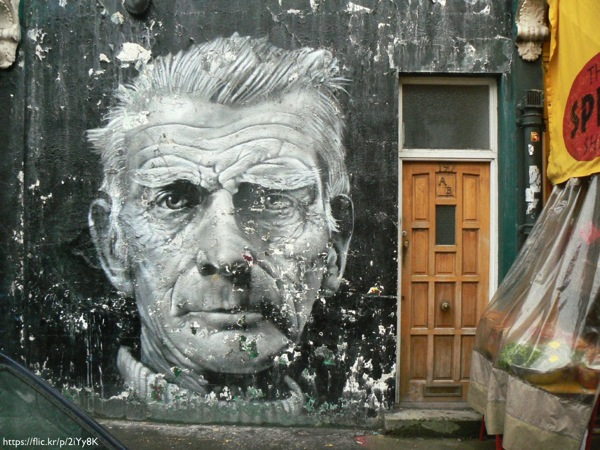 A building wall with street art of Samuel Beckett's face on it