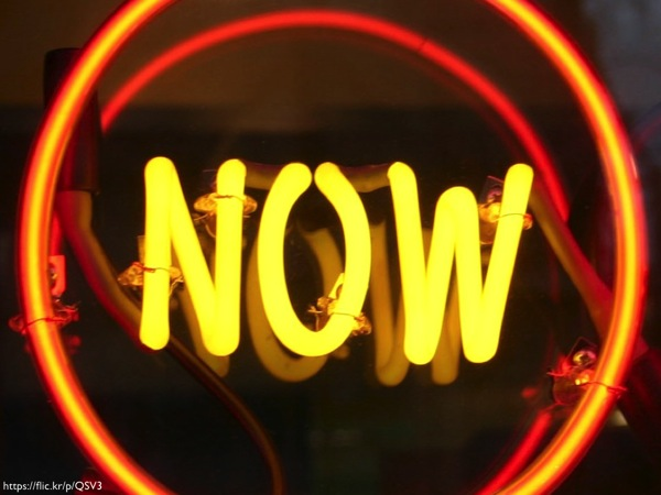 The word 'NOW' written in yellow neon lights