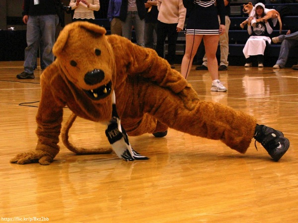 The Penn State Nittany Lion doing one-armed pushps on the floor of a basketball court