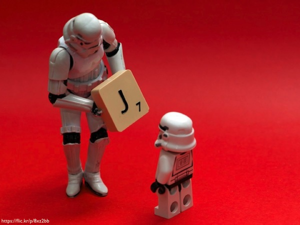 A storm trooper figurine showing a stormtrooper LEGO minifig a Scrabble tile with the letter 'J' on it