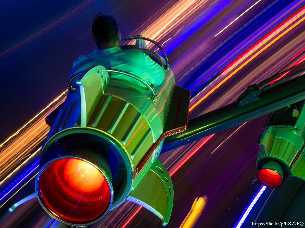 A rocket ride at Disney World shot at night and from behind