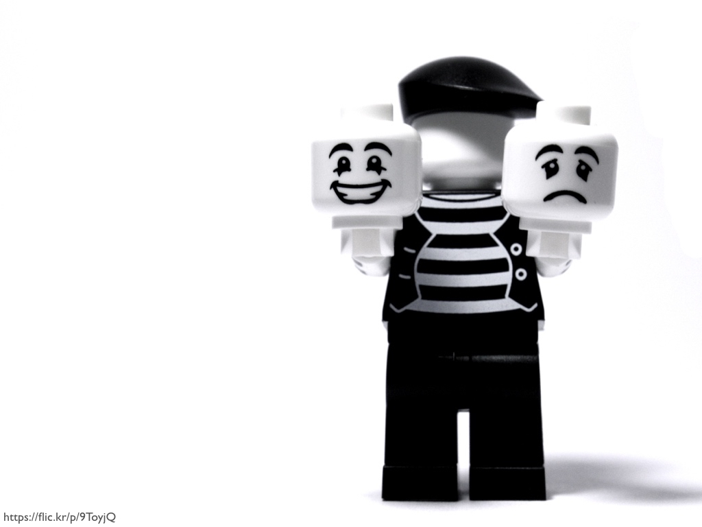 A LEGO minifig of a mime holding a smiling face and a sad face