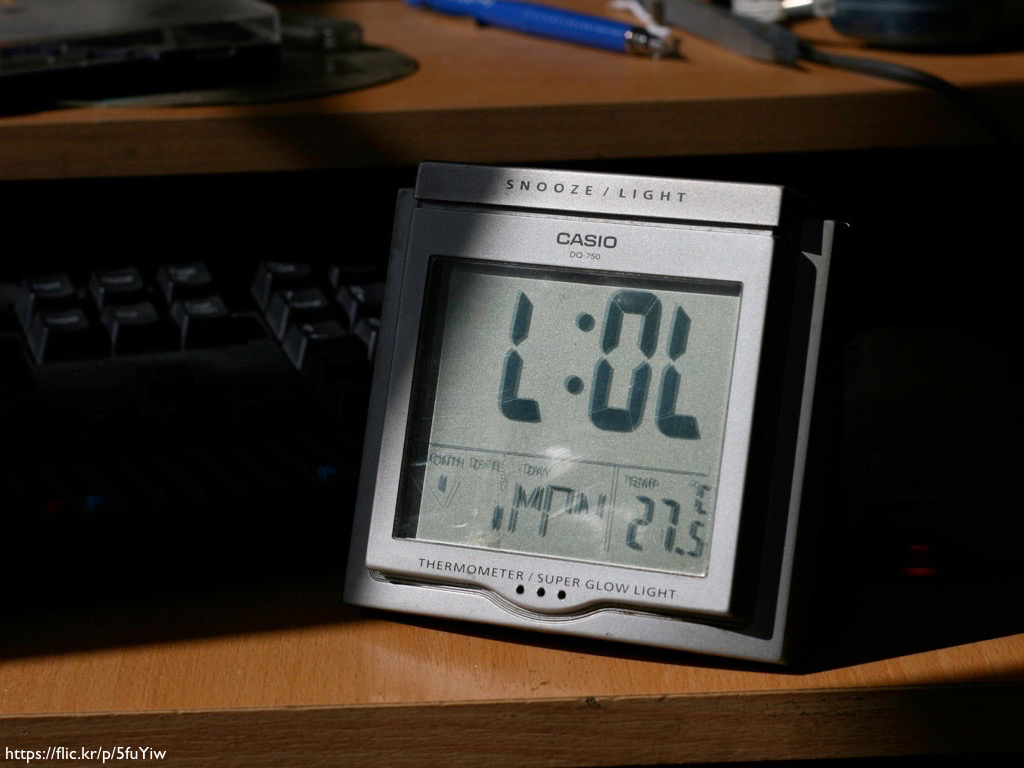 A brken LCD alarm clock that reads 'L:OL'