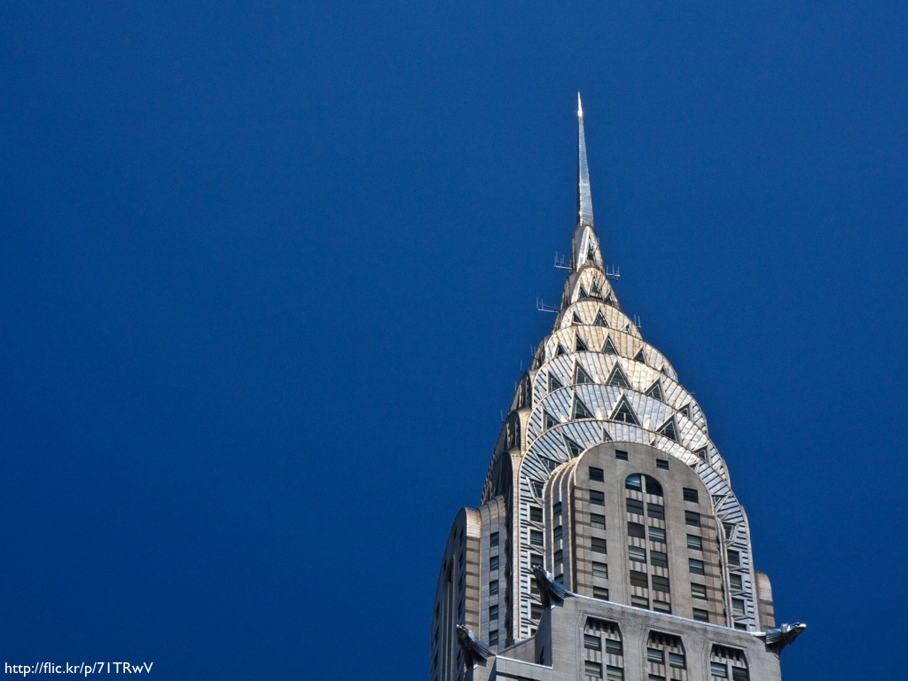 The spire of the Chrysler Building shot against a cloudless blue sky.