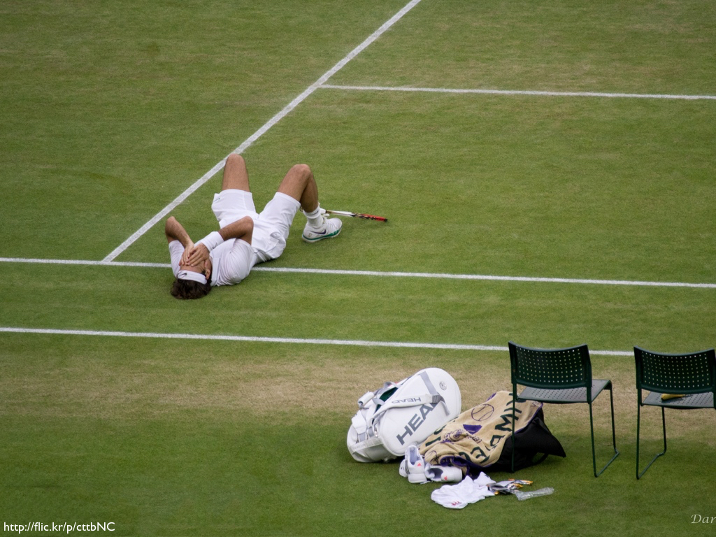 Roger Federer on his back in the court grass with his hands covering his face after winning Wimbledon.