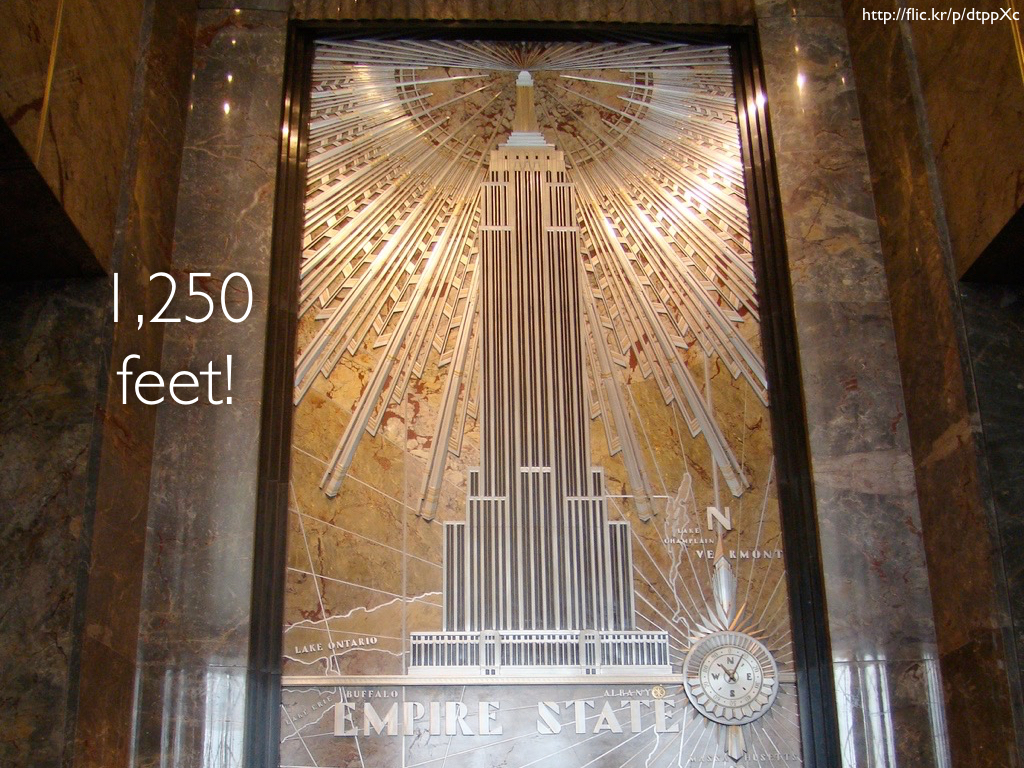 A bronze relief of the Empire State Building from its inside lobby with the words '1,250 feet!' on it.