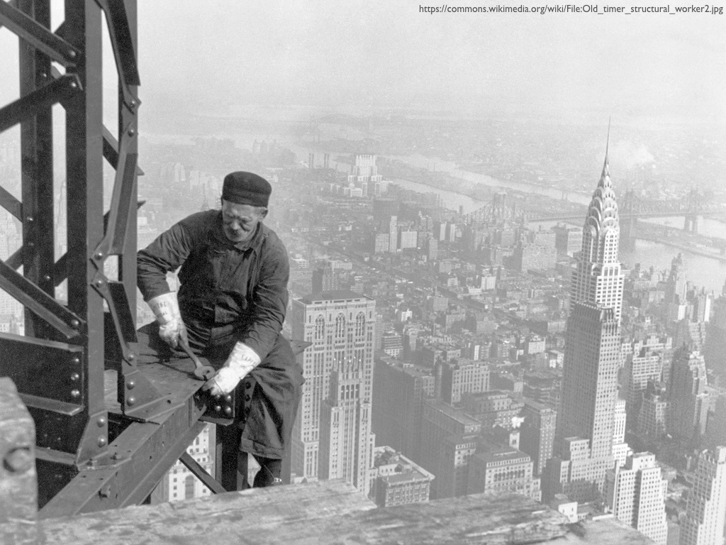 A photograph of a man sitting on a girder building a skyscraper in the 1930s.