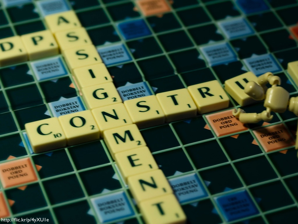 A wooden modeling figure building the words 'assignment' and 'construct' against a Scrabble board.