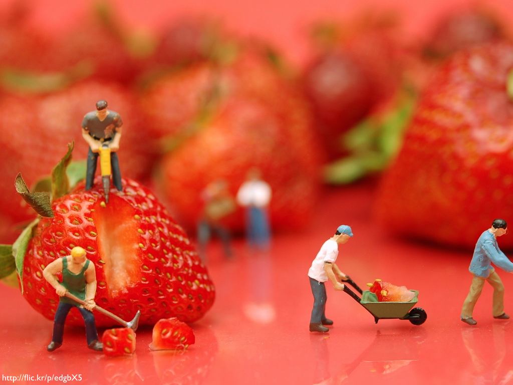 Miniature workmen figures set against a large backdrop of strawberries so it looks like they are mining the fruits.
