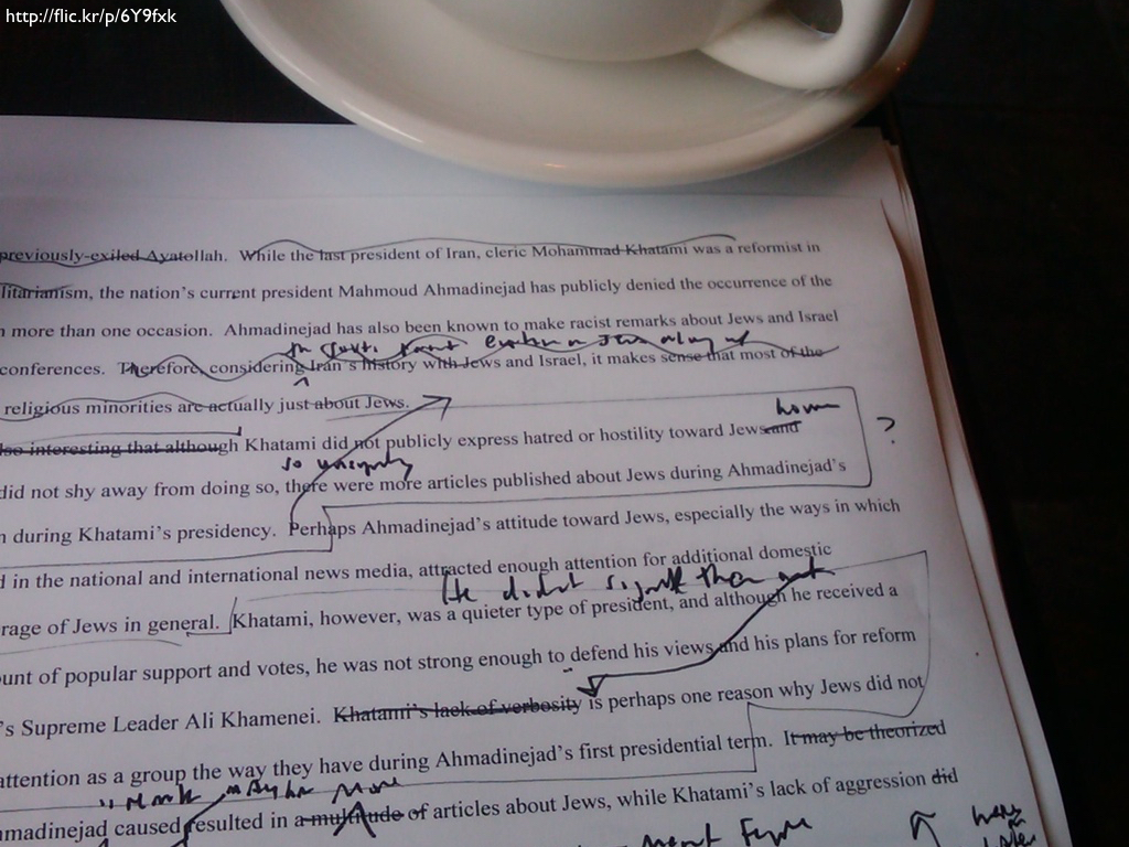 A printed document with handwritten corrections next to the edge of a coffee cup.
