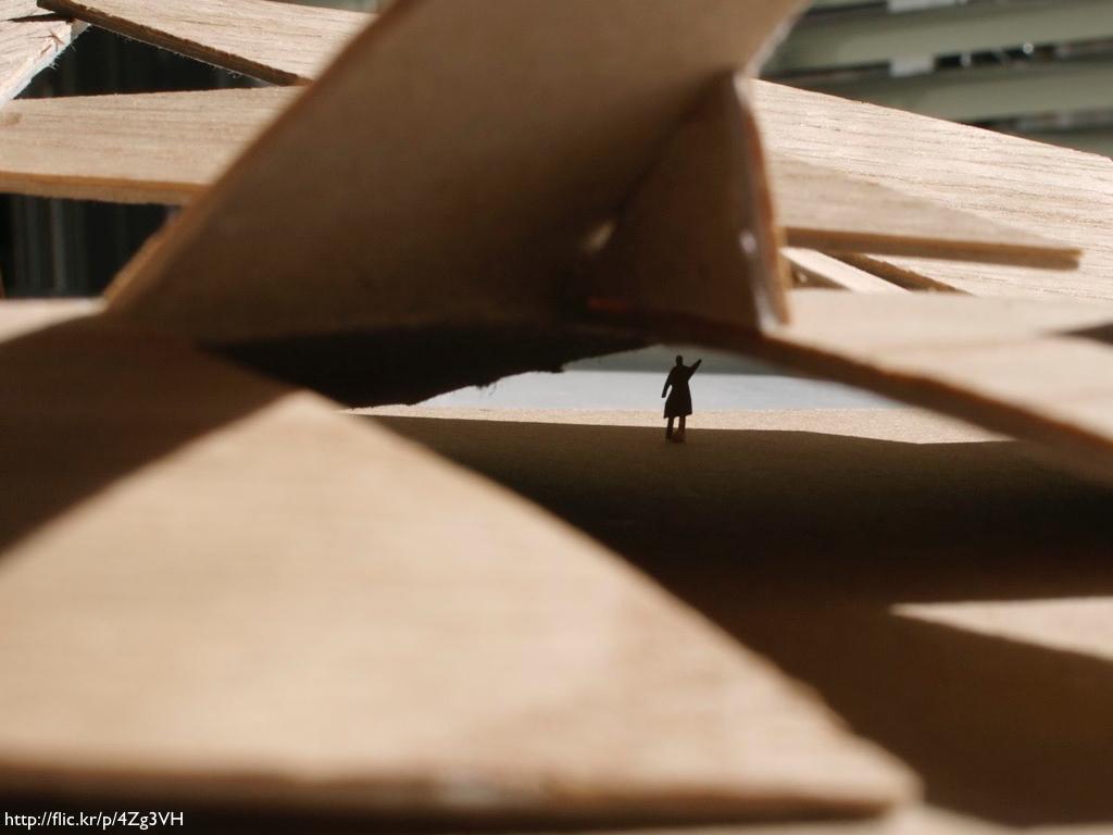 A picture of a small figure under an architectural pile of wood.