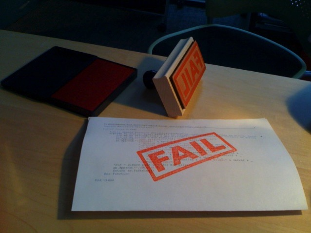A piece of printed paper with a red 'FAIL' stamped on it, with the rubber stamp and ink pad sitting nearby.