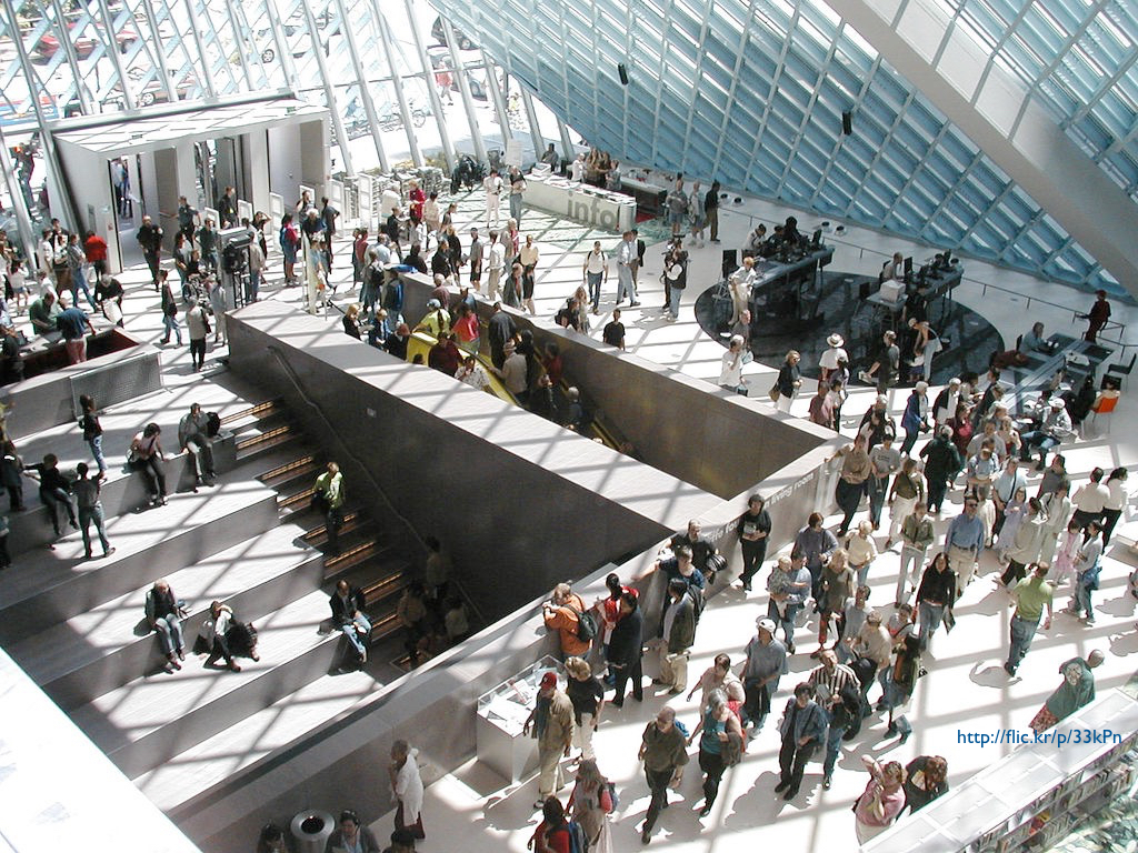 A photograph of the interior of the Seattle Public Library, with large crowds moving through the building.