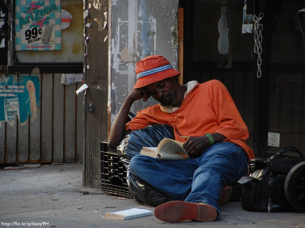 A person who appears to be homeless reading from a battered paperback.
