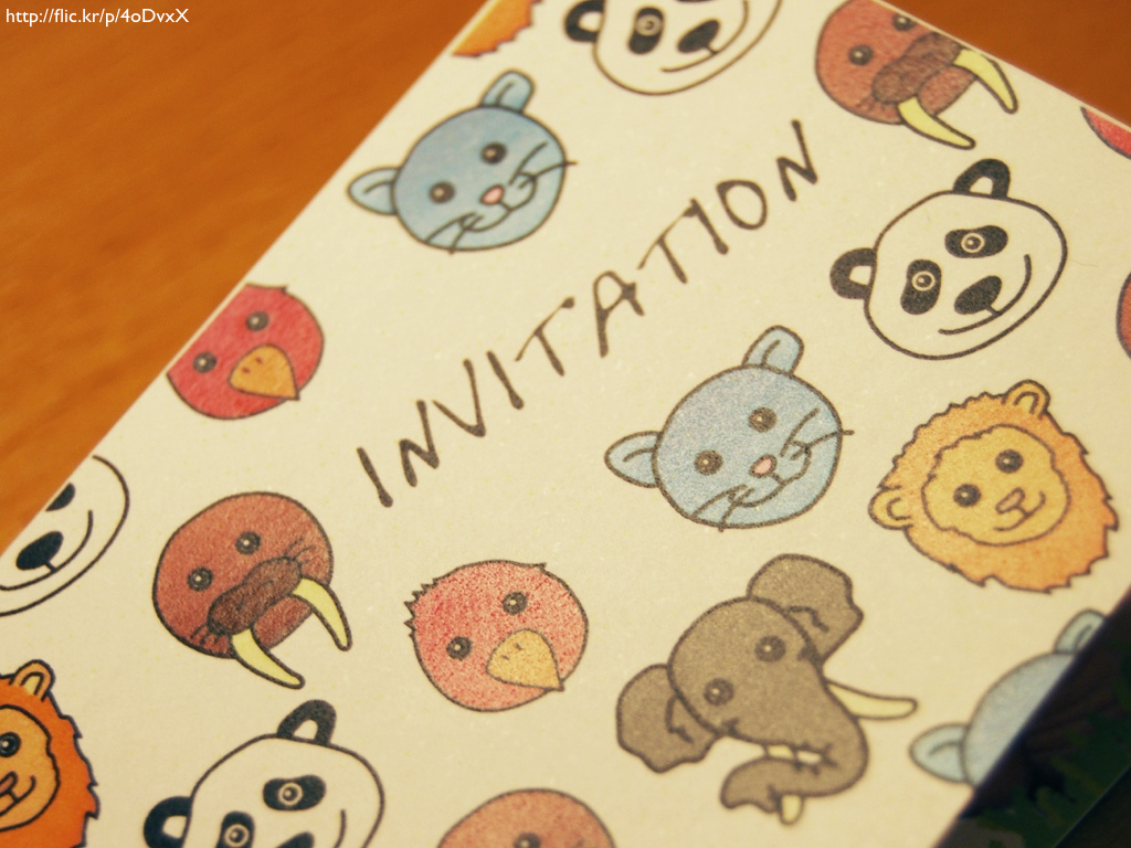 An invitation to a party with happy animal faces on it.