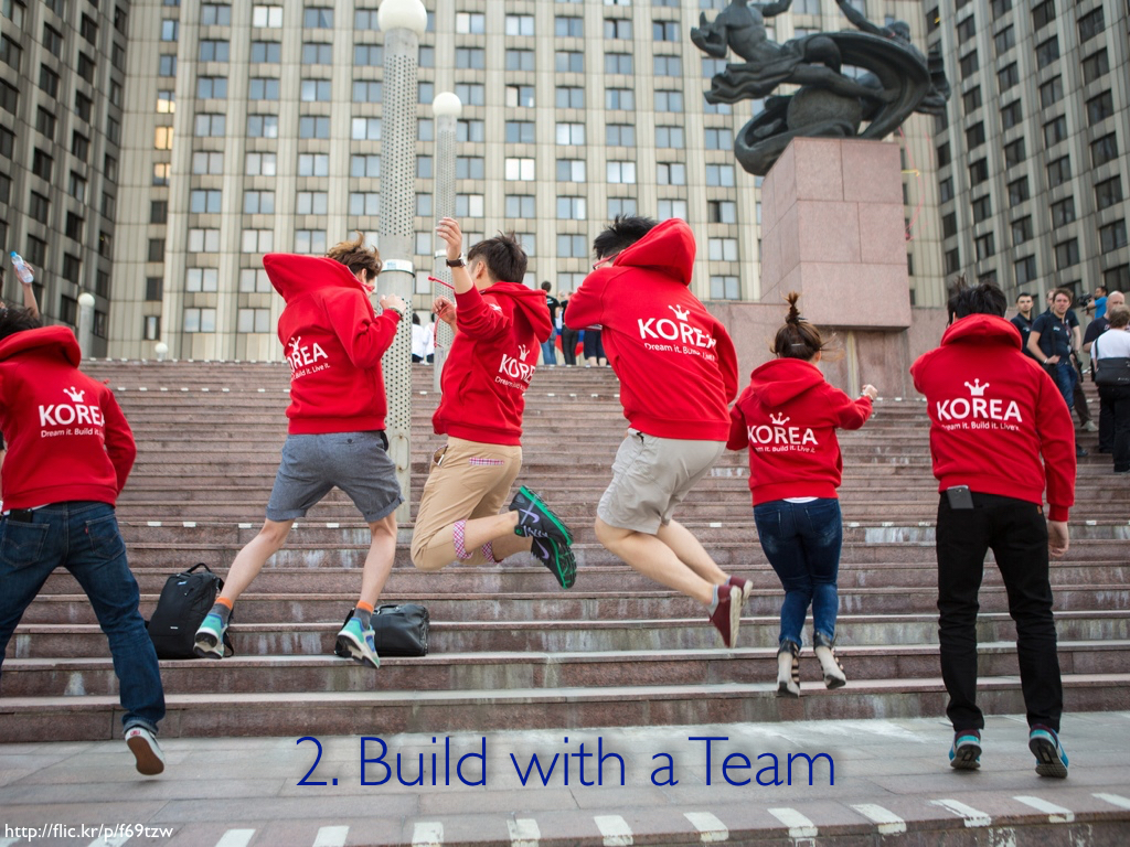 A group of teenagers in red sweatshirts jumping in the air in sync. The caption reads '2. Build with a Team.'