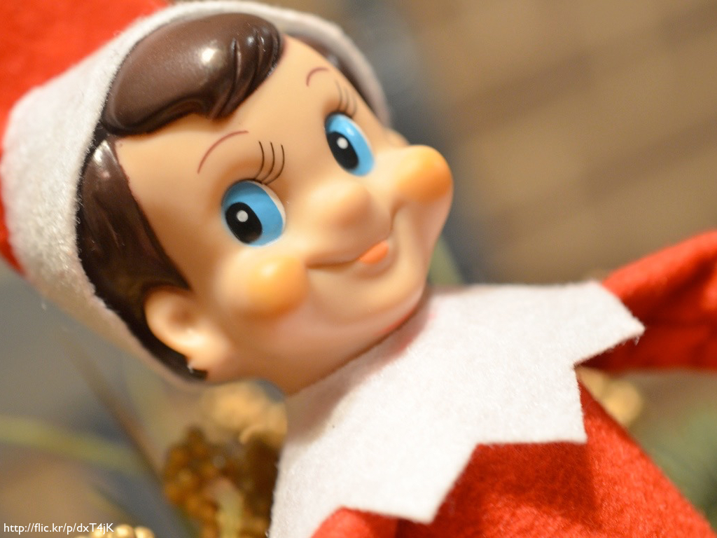 An 'Elf on the Shelf' plastic elf in a red and white suit.