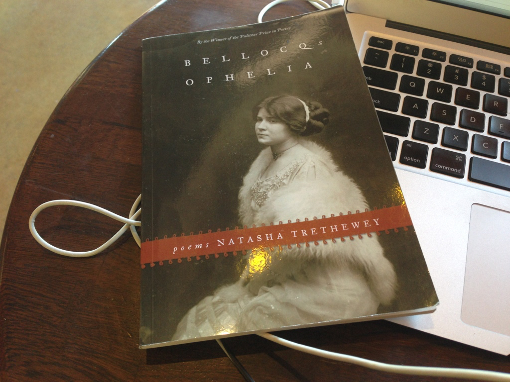 Natasha Trethewey's book, *Bellocq's Ophelia* sitting on top of a MacBook Air.