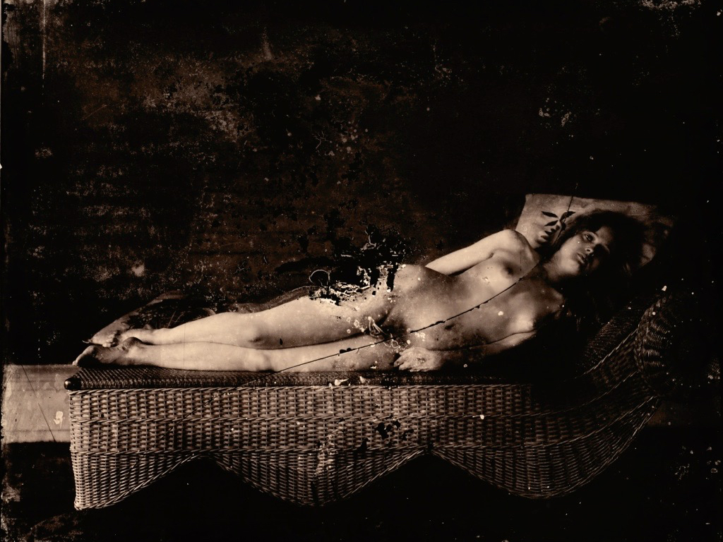 One of Bellocq's photographs, a nude woman reclining on a wicker divan. The photographic plate was cracked and damaged.