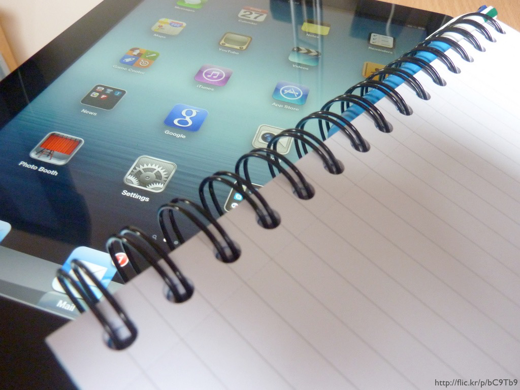 An iPad and a flexi-ring notebook.