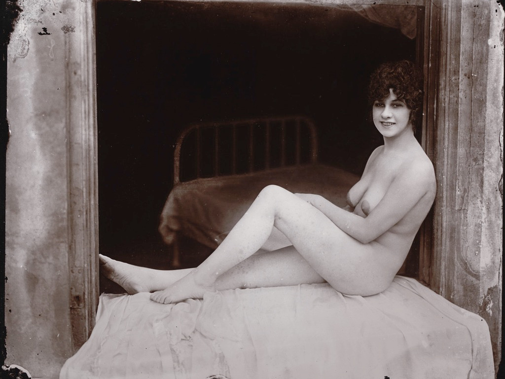A Bellocq photograph of a nude sitting in a window frame with an iron bed in the background.