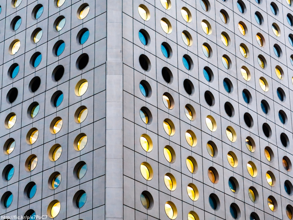 The side of a building with round, porthole-like windows set in concrete in regular intervals.
