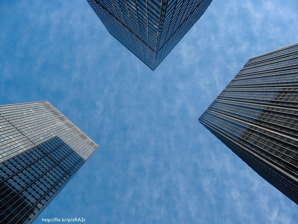 A photograph of three skyscrapers from the perspective of someone standing on the ground and looking up at them.