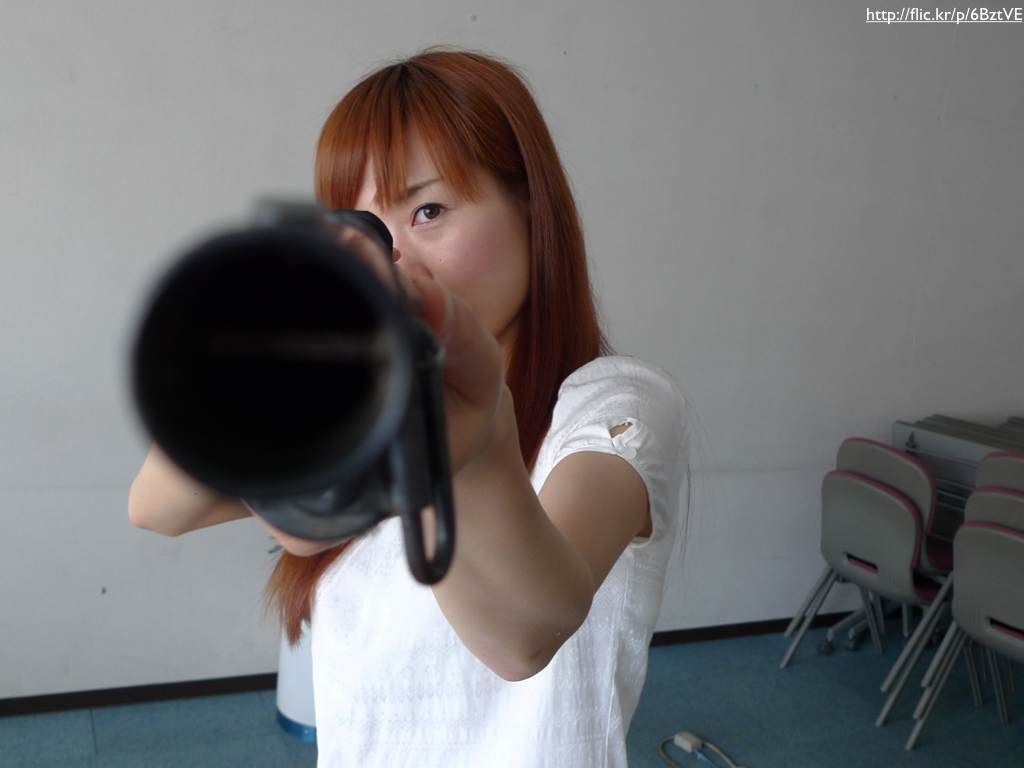 A woman pointing a shotgun's muzzle at the camera.