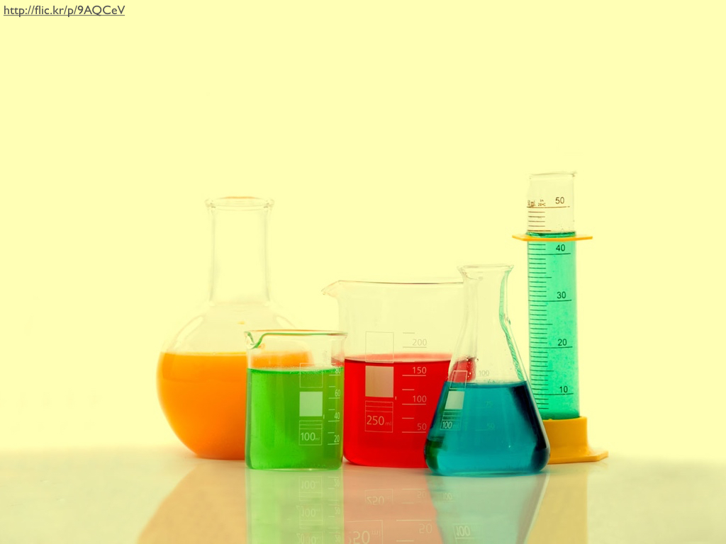 A collection of beakers, flasks, and graduated cylinders filled with colored liquids.