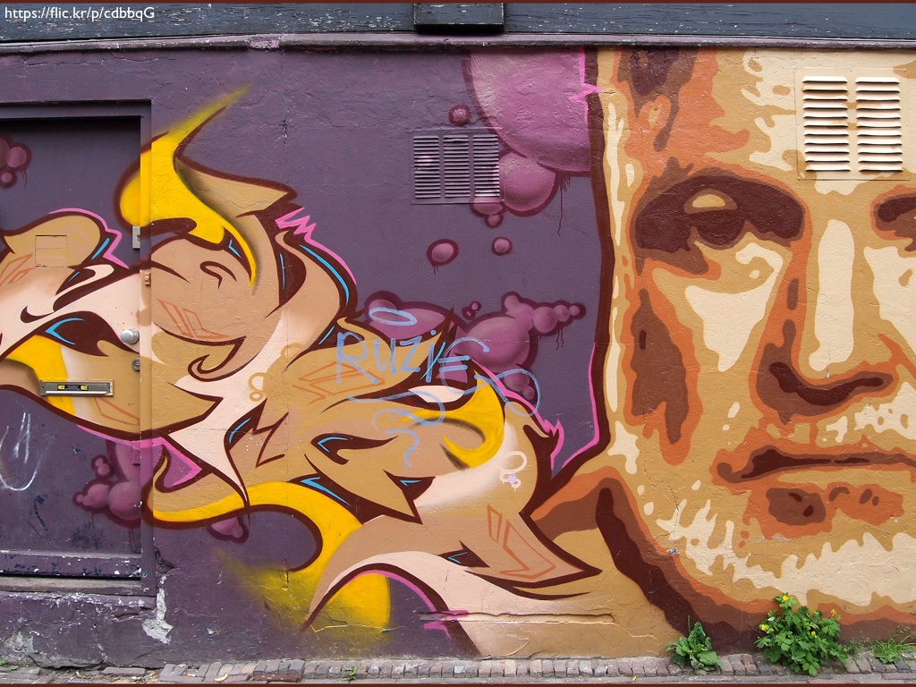 A building with street art of Ernest Hemingway's face painted on it in oranges and purples.