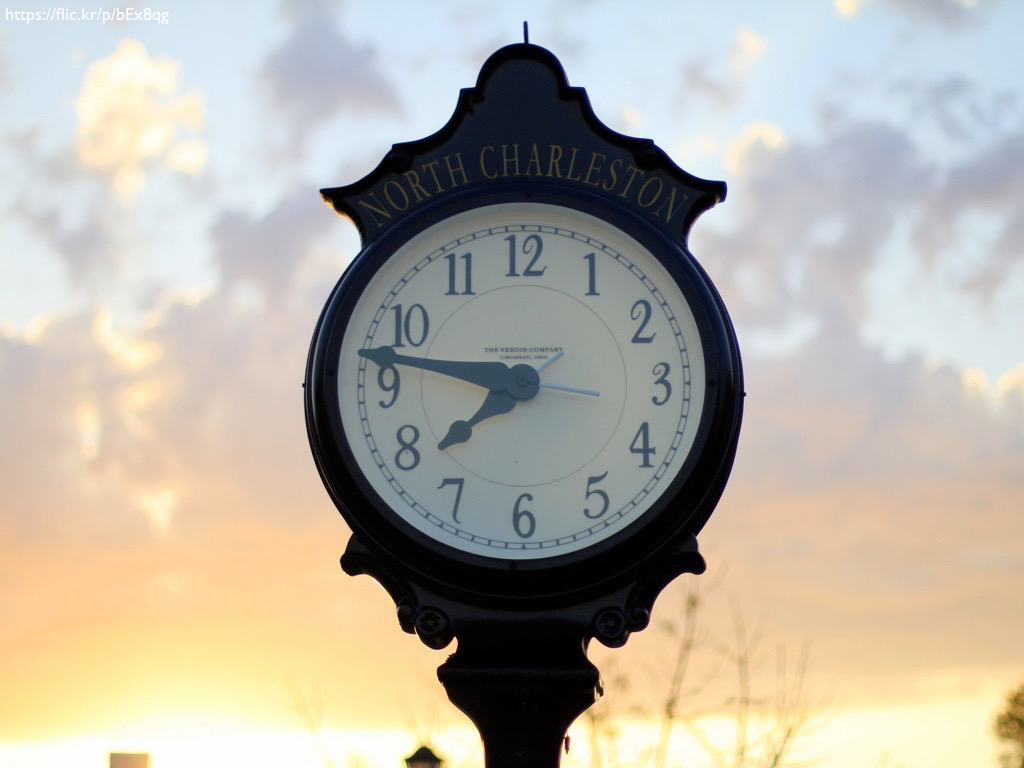 A clock on a metal stand, against a sunset.