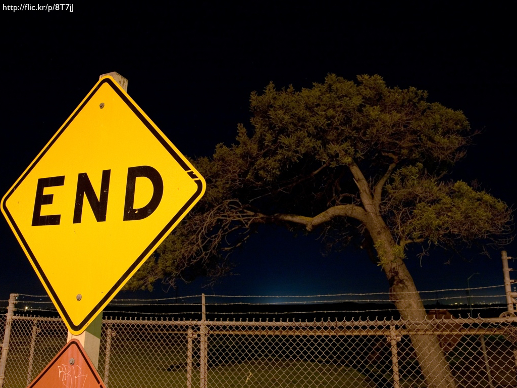 A photograph of a construction sign that reads 'END' against a nighttime backdrop.
