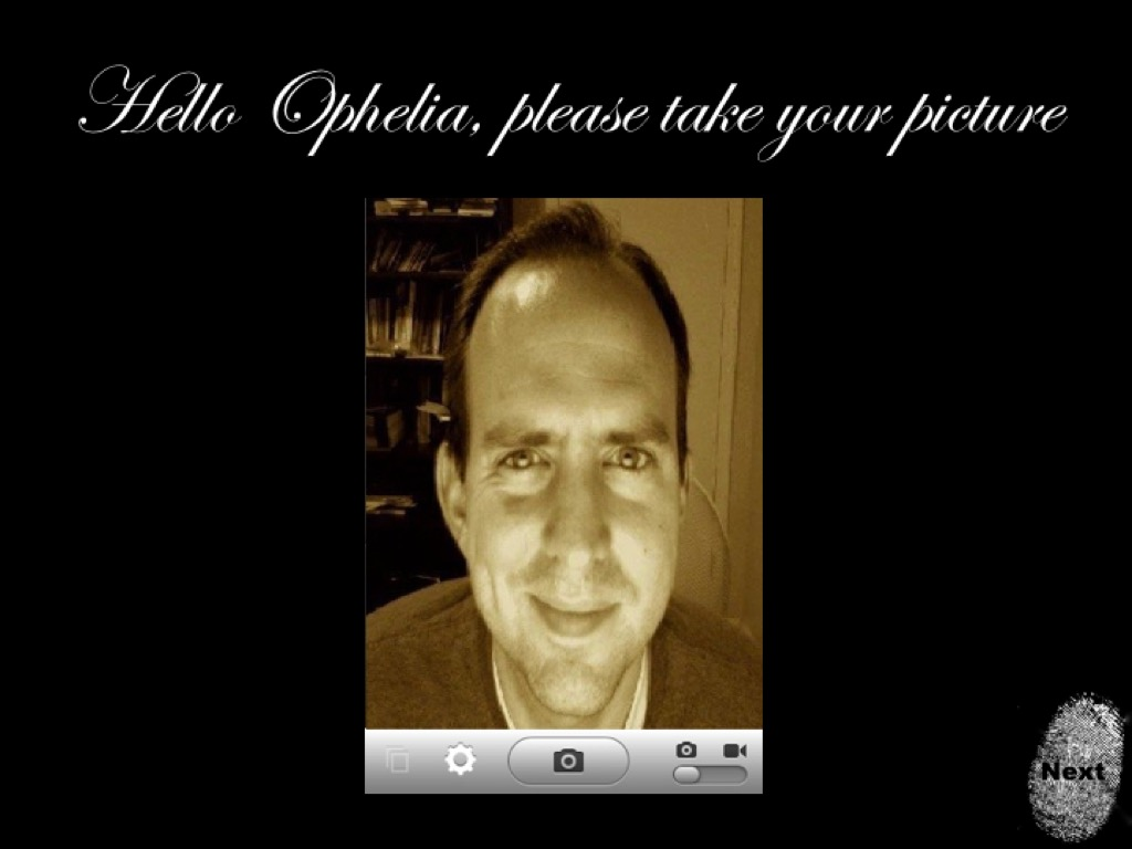 A screenshot of a student designed app showing the iPad camera interface and the prompt, 'Hello Ophelia, please take your picture.' For humor, the students used my picture on the app.