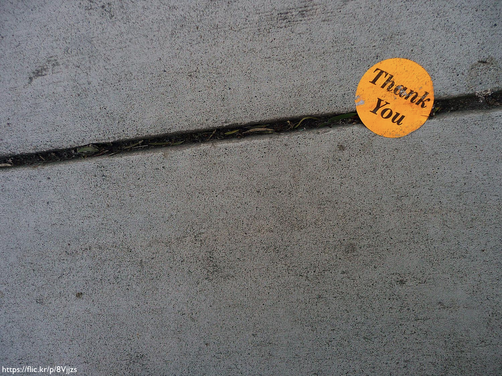 An orange, weatherd 'Thank you' sticker on a sidewalk