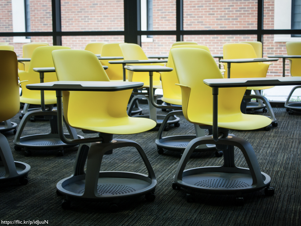 A group of yellow chair / desks in a classroom