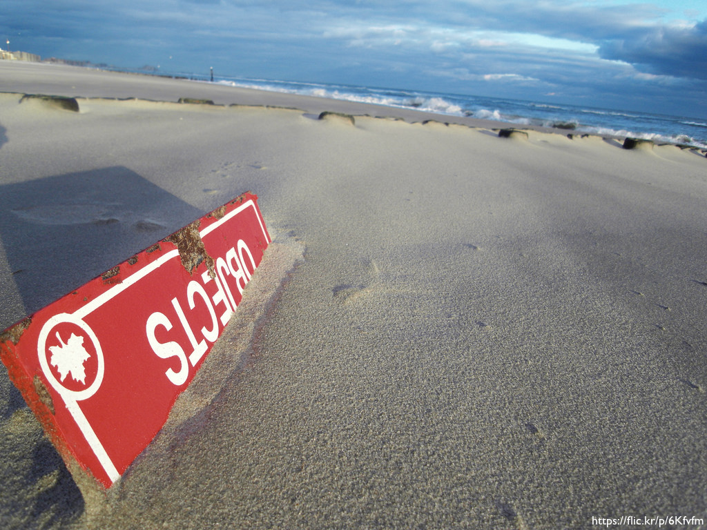 A red sign buried almost completely in the sand at a beach. Only the word 'Objects' is visible.