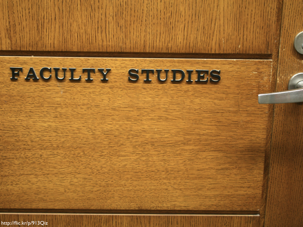 A wooden door with the words 'Faculty Studies' on it in plastic letters