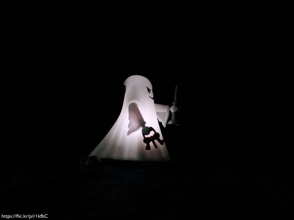 A Playmobil ghost figure, lit up against a black background