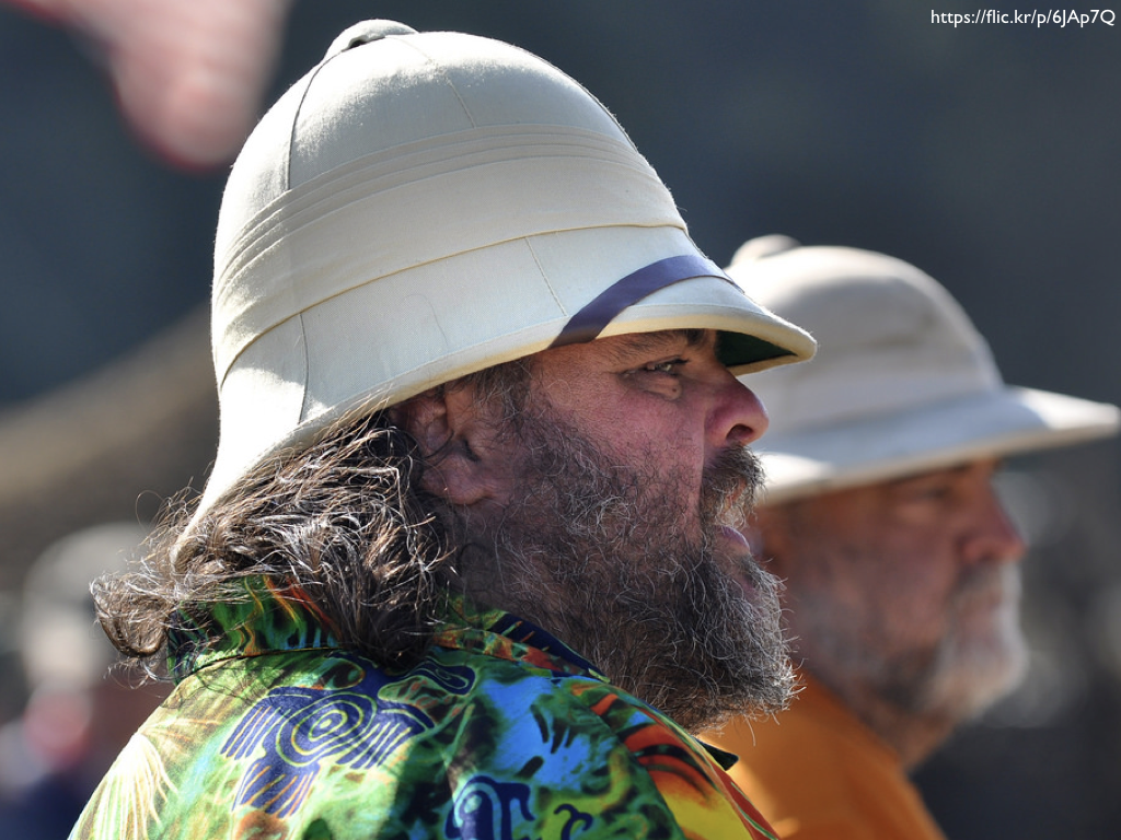 Two men with bears wearing pith helmets.