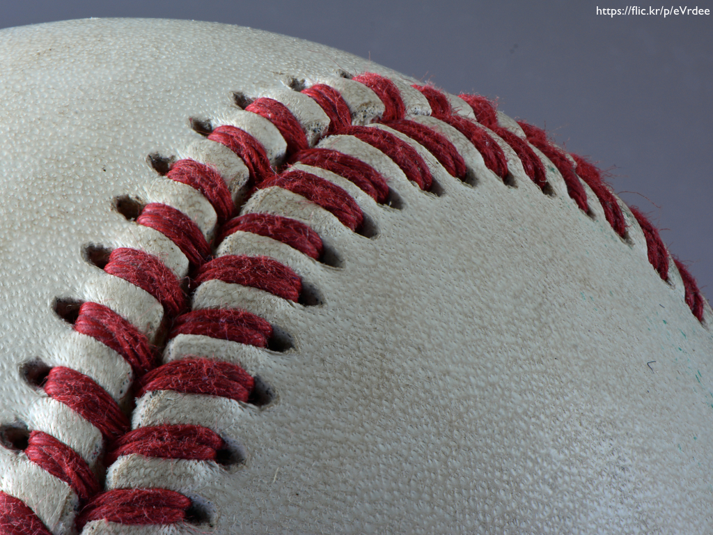 A close-up photograph of the threads on a baseball